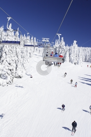 Skiers enjoying the slopes stock photo, View of a ski slope taken from a chair lift by Mark Yuill