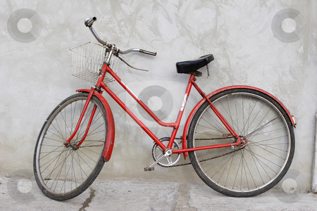 Old red bicycle leaning against a wall stock photo, Old retro bicycle leaning against a wall by Mark Yuill