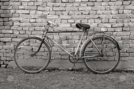 Old bicycle leaning against a wall stock photo, Old retro bicycle leaning against a wall by Mark Yuill