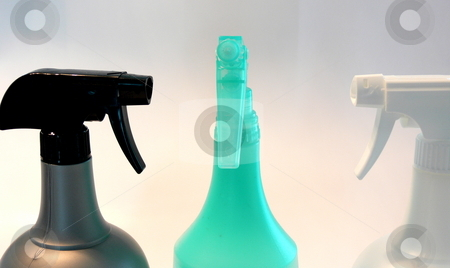 Sprayers stock photo, Three spray bottles facing one another, set against a white background by Martin Darley