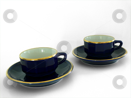 Coffee Cups stock photo, Two dark blue gold-rimmed espresso cups sitting on matching saucers; on a grey/white background by Martin Darley