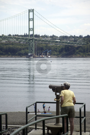 Tacoma Narrows Bridge stock photo, July 14, 2004 :  A park patron looks through a telescope at the Narrows Bridge Park in Gig Harbor, Washington.  The park has a telescope set up so people can get a up close look at the construction of the new Narrows Bridge thats being built. by Jesse Beals