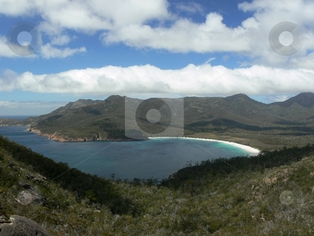Perfect Bay, Perfect Day stock photo, Fluffy white clouds dapple shade on the land surrounding a pure white beach which slides into an azure sea. Wineglass Bay, Tasmania, Australia by Martin Darley