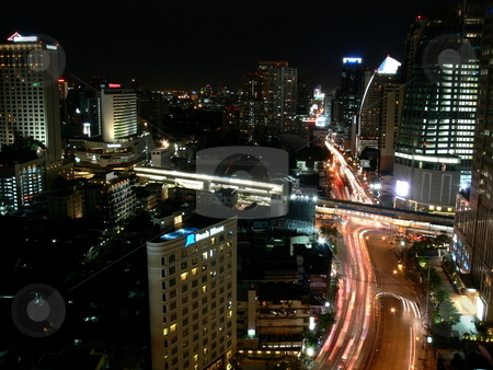 Busy Road stock photo, An arterial road slices through the high rise buildings of the city, with lights from a stream of cars blurred in their night time haste. Asoke intersection, Sukhumvit, Bangkok, Thailand by Martin Darley