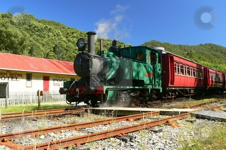 Steam Train stock photo, A green locomotive hauls red carriages past a period hotel on the West Coast Wilderness Railway, as it travels from Queenstown to Strahan. Tasmania, Australia by Martin Darley