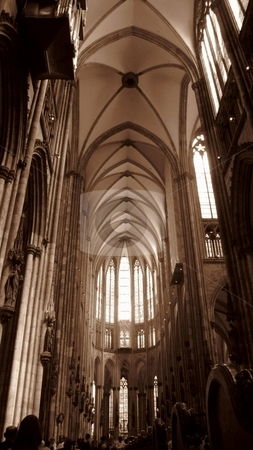 Cologne Cathedral stock photo, The K???lner Dom towers above parishioners and tourists; Sunlight streams through it's stained-glass windows. monochrome sepia shot. North Rhine-Westphalia, Germany by Martin Darley