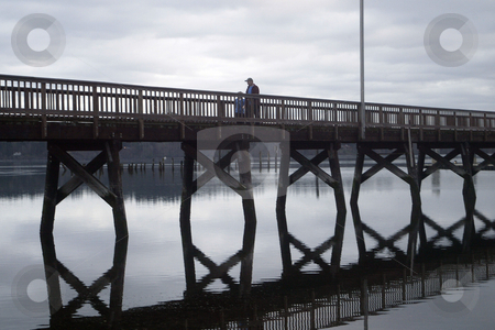 The Silverdale dock stock photo, March 9, 2004 : A father and son could be seen walking along the Silverdale dock located in Silverdale, Washington.  The dock reflecting off the water during an afternoon light rainstorm. by Jesse Beals