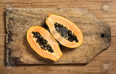 Papaya fruit sliced stock photo, Papaya fruit sliced on a wooden cutting table by Pablo Caridad