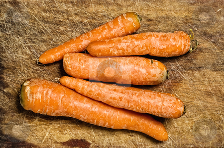 Bunch of carrots stock photo, Bunch of carrots over an old wooden table. by Pablo Caridad