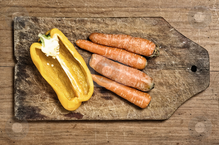 Yellow bell pepper and carrots. stock photo, Yellow bell pepper and carrots on a wooden cutting table. by Pablo Caridad
