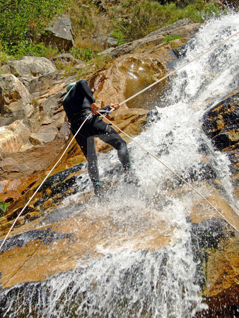 Men descending on rappel stock photo, Men descending waterfall in Portugal by Paulo Resende