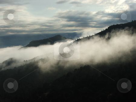 Morning Fog on Arizona Verde Mountains stock photo, Morning fog hangs along the Verde Mountain ridges above Camp Verde, Arizona as the sun tries to break though the cloudy sky. by Dennis Thomsen