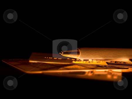 Credit card with pen stock photo, Golden credit cards cut with pen on black reflective surface by Laurent Dambies