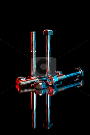Nuts and bolts stock photo, Industrial looking nuts and bolts on a reflective surface by Vince Clements