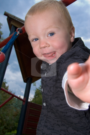 Cheeky boy stock photo, A little boy standing on the playground looking cheeky into the camera by Alexander L?