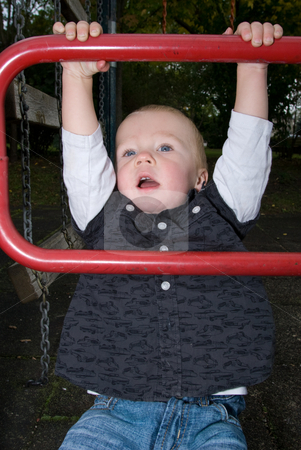 Do the cheeky funky monkey stock photo, A little boy chinning the bar at the playground by Alexander L?