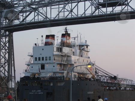 Freighter Arrives at Duluth stock photo, The Argolake, a Lake Superior freighter passes under the lift bridge in the canal opening to the Duluth, Minnesota harbor.  These cargo ships move iron ore (taconite) and other commodities, heavy equipment, and goods through the Great Lakes waterways. by Dennis Thomsen