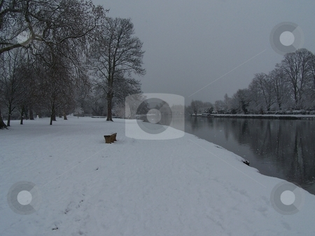 Bench in the snow alongside the Thames stock photo, A rare snowy day in Oxford, walking along the Thames at the bottom of Christ Church Meadow. by JKJ Anderson