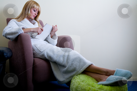 Reading a book in her room stock photo, Blond model in bathrobe and slippers by Frenk and Danielle Kaufmann