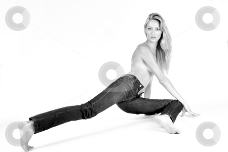Portrait of a young woman in jeans stretching her leg stock photo, Studio portrait of a blond woman in only jeans in a creative pose by Frenk and Danielle Kaufmann
