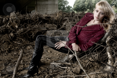 Laying between dead trees stock photo, Fashion shoot under a bridge by Frenk and Danielle Kaufmann