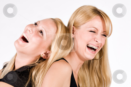 Two sisters having fun stock photo, Two sisters sitting back to back laughing out loud by Frenk and Danielle Kaufmann