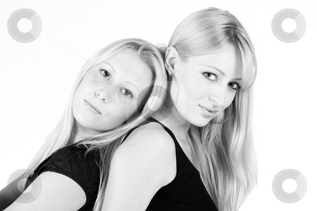 Loving sisters back to back stock photo, Studio portrait of two sisters looking sensual into the camera by Frenk and Danielle Kaufmann