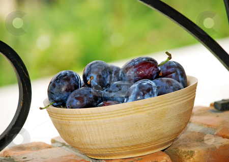 Plums wooden bowl stock photo, Blue ripe plums in wooden bowl over brick fence by Julija Sapic