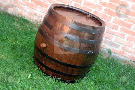 Wood Wine barrel stock photo, Old  wooden wine brown barrel over grass and brick wall by Julija Sapic