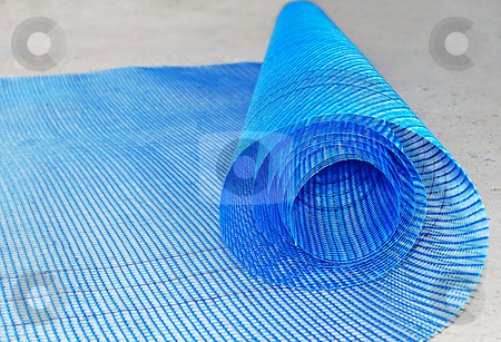 Plastic net roll stock photo, Blue plastic net roll rolled out over concrete by Julija Sapic