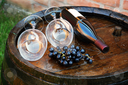 Wood Wine barrel stock photo, Glasses and bottle of wine lying over wooden barrel by Julija Sapic