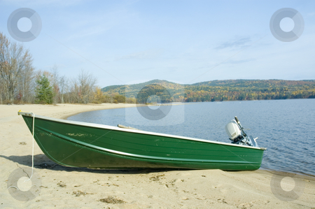 Boat stock photo, A small green boat near the shore by Vlad Podkhlebnik