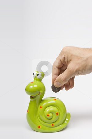Snail Saving stock photo, A male hand deposits a coin into a green snail shaped savings box by Steve Smith