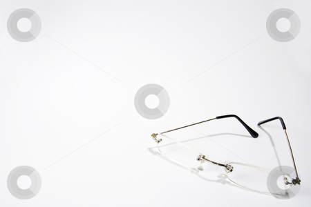 Reading Glasses stock photo, A pair of reading glasses partially folded on the lower right-hand side of a white frame by Steve Smith