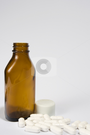 Brown bottle and pills stock photo, A brown bottle, opened with pills around the base by Steve Smith