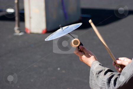 Cymbal stock photo, A hand held cymbal being played by a street musician by Nicholas Rjabow