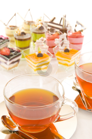Tea and confectionery stock photo, Freshly brewed red tea in a glass cup on a shiny saucer, with some colorful confectionery on a white background. by Nicolaas Traut