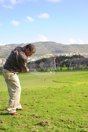 Senior golfer in action stock photo, An elderly retired golfer in action on a practice range, hitting the ball with a club. by Nicolaas Traut