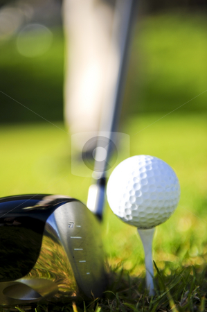 Golfer in action stock photo, A golfer in action on a practice range, hitting the ball with a club. by Nicolaas Traut