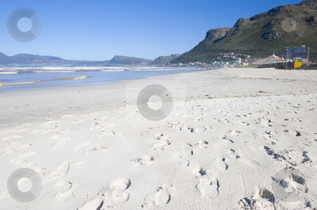 White sandy beach stock photo, A beautiful white sandy beach with footprints. The seashore, some mountains and colourful dressing huts are visible in the background. by Nicolaas Traut