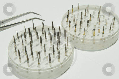 Dentistry instruments stock photo, A variety of dentistry drillbits in their holders, with a pair of tweezers. by Nicolaas Traut
