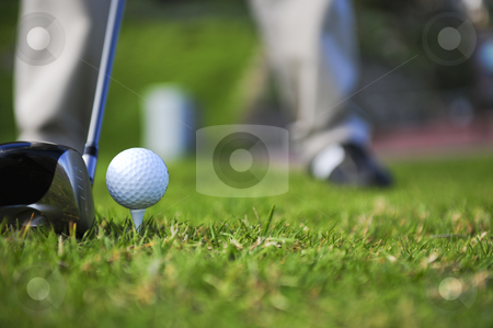 Golfer in action stock photo, A golfer in action on a practice range, lining up his driving wood with a ball on a tee. by Nicolaas Traut