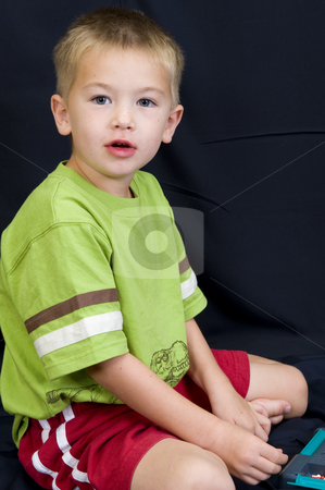 Little boy playing on black background stock photo, A cute little boy playing on a black background. by Nicolaas Traut