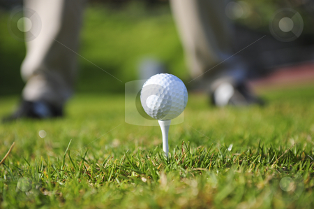Golfer in action stock photo, A golfer in action on a practice range. Focus on the ball and tee, with golfers legs faded out in the background. by Nicolaas Traut