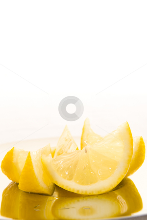 Fresh sliced lemon stock photo, Freshly cut slices of lemon on a shiny plate with a white background. by Nicolaas Traut