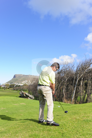 Handsome young golfer in action stock photo, A golfer in action on a practice range, hitting the ball with a club. by Nicolaas Traut