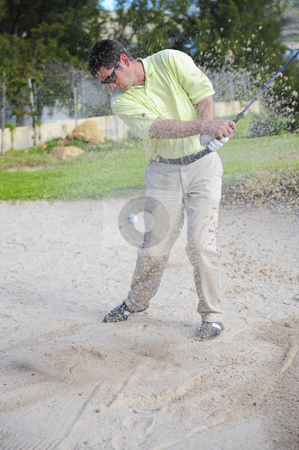 Golfer playing out of a sand trap stock photo, A professional golfer playing a shot out of a sand-trap with excellent control. by Nicolaas Traut