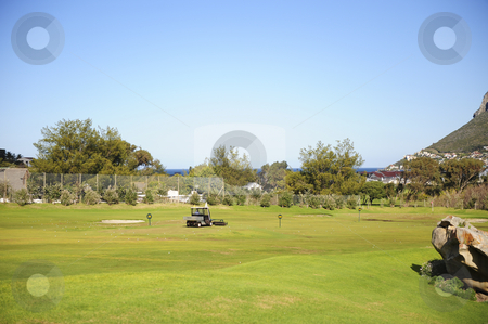 Golf driving range stock photo, A beautifully maintained practice or driving range with distance markers for golfers to practice on. A motorized vehicle is in the process of picking up balls on the range. by Nicolaas Traut