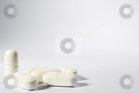 Medical Pills stock photo, A group of pills on the lower left-hand side of a white frame with one standing up by Steve Smith