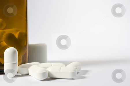 Pills and bottle stock photo, A group of pills on the lower left-hand side of a white frame with one standing up nest to a brown bottle by Steve Smith
